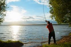 Fisherman on the lake. Man throws spinning rod, back view . Fishing at sunset. Setting sun, lake shore in frame of trees.