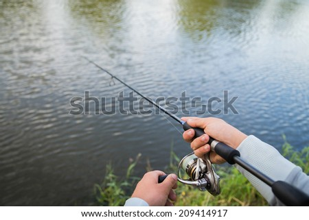 Fisherman on the river bank. Man fisherman catches a fish. Fisherman in his hand holding spinning. Fishing, spinning reel, fish, Breg rivers. - The concept of a rural getaway. Article about fishing. #209414917