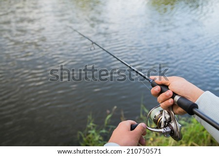 Fisherman on the river bank. Man fisherman catches a fish. Fisherman in his hand holding spinning. Fishing, spinning reel, fish, Breg rivers. - The concept of a rural getaway. Article about fishing. #210750571