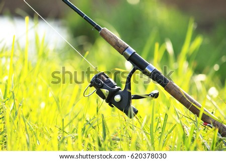 Fisherman's fishing rod with inertia-free coil in summer on shore of lake #620378030