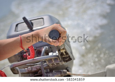 Fisherman's hand and boat engine on river