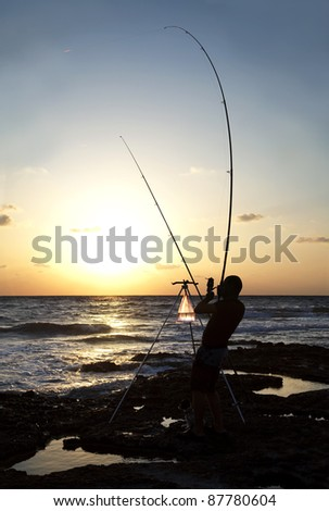 Fisherman silhouetted against the Mediterranean Sea sunset - stock photo