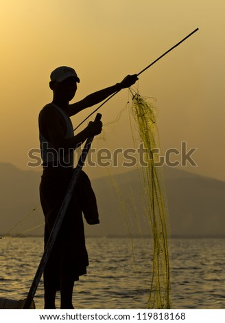 Fisherman silhouetted against the setting sun in Inle Lake, Myanmar/Burma