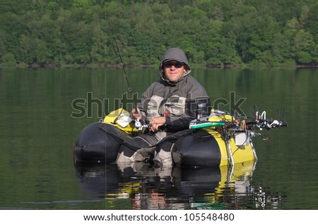 Fisherman, sitting in a comfortable float tube, wait for a fish