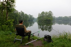 Fisherman sitting on the chair and fishing during cloudy day