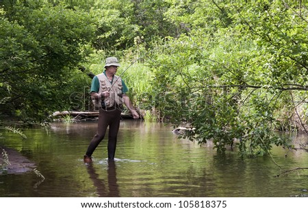 fisherman snagged on a branch in a small trout stream
