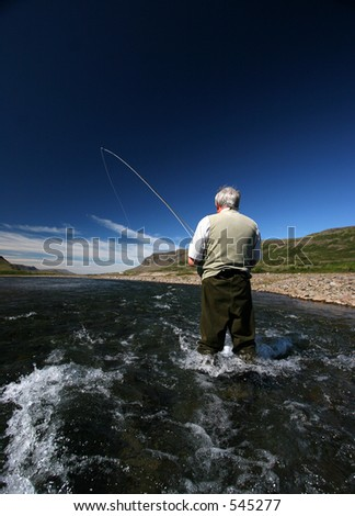 Fisherman standing in river with a fish on the line