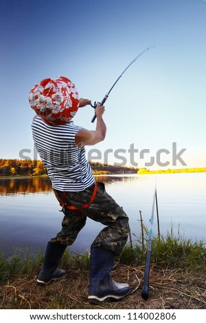 Fisherman standing on a coast of pond and pulling a fish
