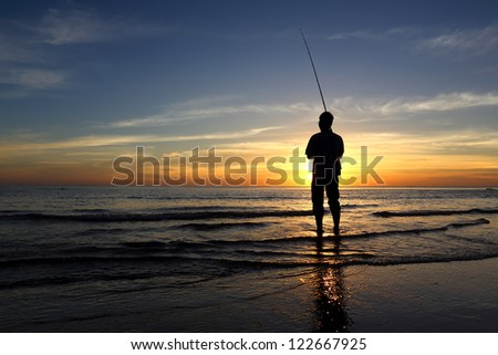 Fisherman standing on a pier at evening sky background in the sea water
