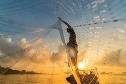 Fisherman throwing fishing net during sunrise in Pak Pra, Phatthalung, Thailand