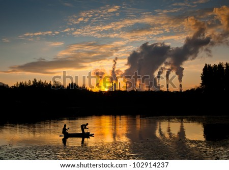 Fisherman throwing net and hot steam from big chimney background.
