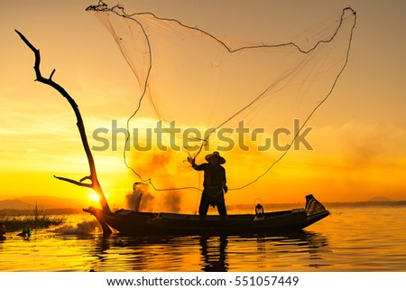 fisherman throwing net catching fish in the lake #551057449