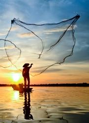 Fisherman throwing out fishing net on the lake. Fisherman throwing net at sunrise