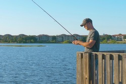 Fisherman throws a fishing tackle into the lake from a wooden pier. Fishing in river. Man fisherman catches a fish. Fisherman with spinning rod catching fish on lake.