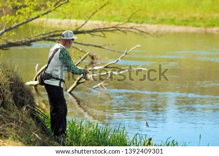 Fisherman trying to do a perfect cast, throwing lure. Spining fishing, angling, catching fish. Hobby and vacation. Photo with shallow depth of field taken at wide open aperture.