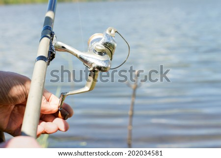Fisherman using a spinning reel for freshwater fishing on a rural lake, close up of his hands and the reel #202034581
