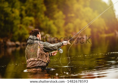Fisherman using rod fly fishing in mountain river. ストックフォト ©