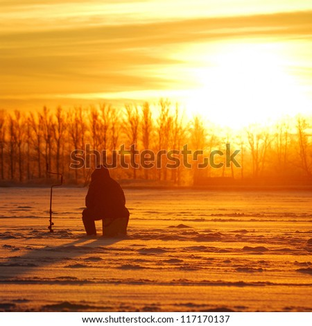 fisherman waiting for fish on ice at the sunrise