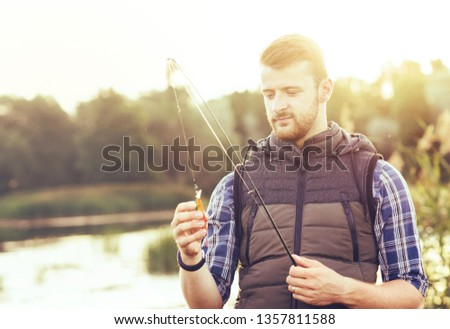Fisherman with a spinning and bait catching fish on a lake or river. Man on a weekend with a fishing road. Hobby and leisure concept.