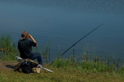 fisherman with fishing rod catching fish, sitting riverside.