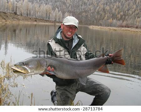 Fisherman with giant taimen in Mongolia