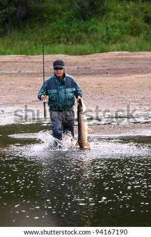 Fisherman with pike fish on the shore of river Uur in northern Mongolia