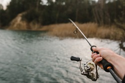 Fisherman with rod, spinning reel on the river bank. Man catching fish, pulling rod while fishing from lake or pond with text space. Fishing for pike, perch on beach lake or pond. Fishing day concept.