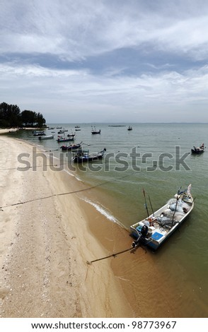 Fisherman wooden boat anchored to a rural golden beach in Penang, Malaysia, against a dramatic blue cloudy sky.