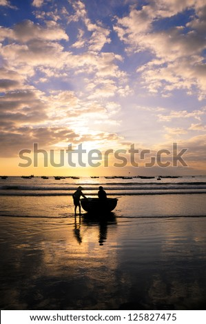 Fishermans are working in sunrise at My Khe beach, Danang, Vietnam