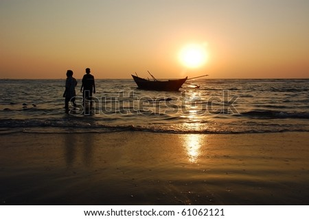 Fishermen are walking away from the fishing boat at the end of the working day at sunset in the Indian state of Goa.