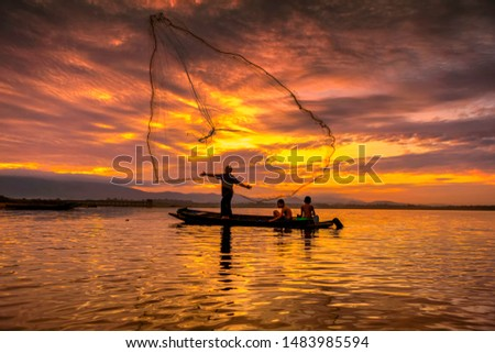 Fishermen Casting are going out to fish early in the twilight sky morning with wooden boats, old lanterns and nets. Concept Fisherman's life style.