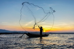 Fishermen Casting fishing early in the morning sunrise with wooden boats. Concept Fisherman's life style. Image is silhouette.