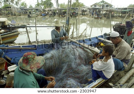 Fishermen fix fishing nets.