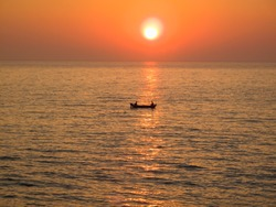 Fishermen in boat at sea with sunset backdrop