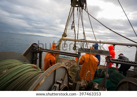 Fishermen in waterproof suits on the deck of the fishing seiner. Morning time. #397463353
