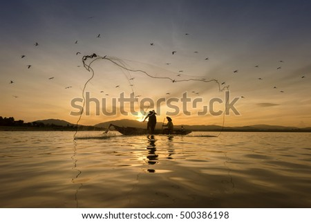 Fishermen is fishing in the river at sunrise surrounding with birds #500386198