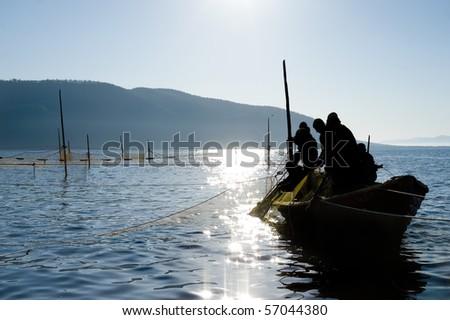 fishermen on a boat haul a seine