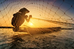Fishermen on fishing boats use fishing equipment at sunset.