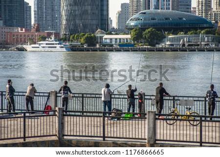 Fishermen on Huangpu river with skyline view of Shanghai skyscraper, China #1176866665