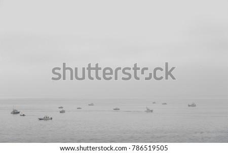Fishermen on  little boats in a foggy day in Mediterranean sea #786519505