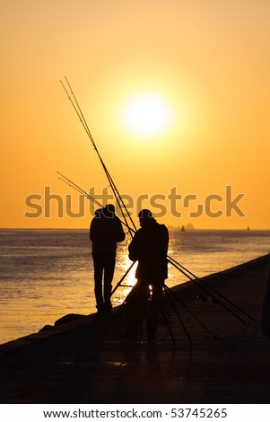 Fishermen on the pier - hazy and yellow sunset from volcano-dust in the air