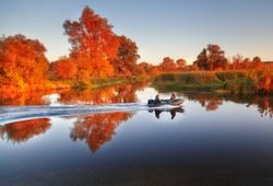 Fishermen sailing fast at rubber powerboat by river making trace at tranquil water surface against beautiful morning scenery with golden color foliage trees at bank. Fishing background.