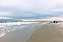 Fishermen walking beach at sunrise in winter on Long Island, New York