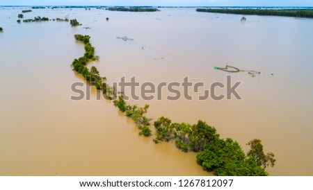 Photo of Fishermens fishing on a fishing boat in river in An Giang province, Mekong Delta, Vietnam on floating water season at sunrise. Top view/ top shots.