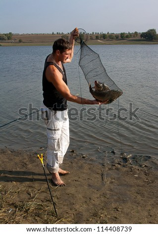 fishers hands lift a net with fish