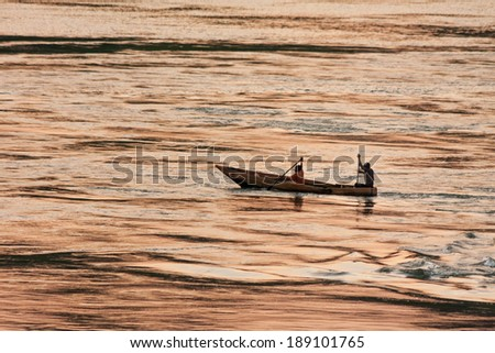 Fishers in boat rows against evening glow reflection in Victoria Nile River background at sunset. Jinja, Uganda, Eastern Africa.