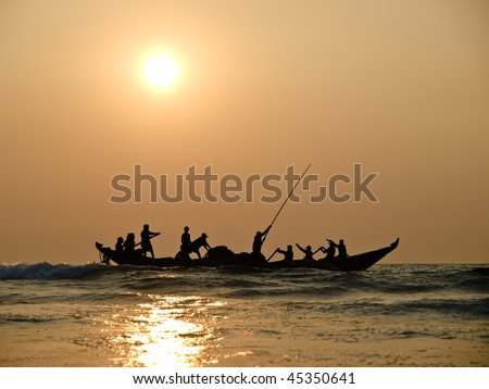 Fishers on boat in sunset on the sea