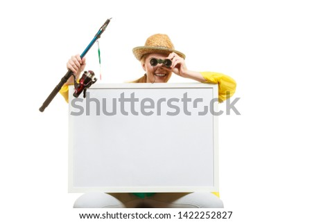 Fishery, spinning equipment, angling sport and activity concept. Happy woman with fishing rod and binoculars holding blank white board with copyspace.