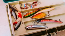 Fishery utensils. Close up picture of professional fishing box with many colorful bait, lures and accessories