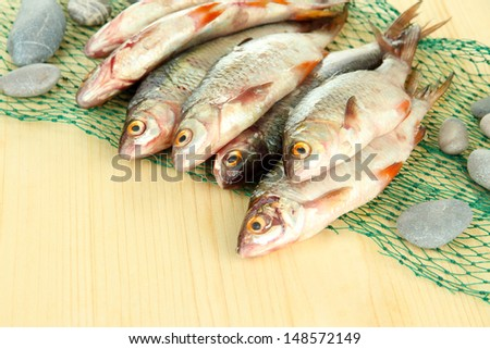 Fishes on fishing net on wooden background #148572149